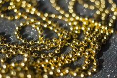 Χρυσές χάντρες σε ένα μαύρο υπόβαθρο Στοκ φωτογραφίες με δικαίωμα ελεύθερης χρήσης