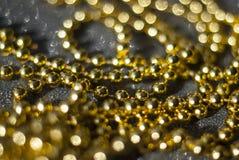 Χρυσές χάντρες σε ένα μαύρο υπόβαθρο Στοκ Εικόνα