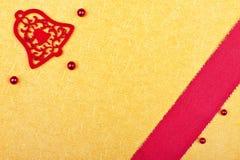 Χρυσή ευχετήρια κάρτα με το κόκκινο κουδούνι Στοκ φωτογραφία με δικαίωμα ελεύθερης χρήσης