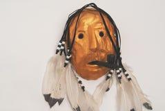 Χρυσή ινδική μάσκα με τον καπνίζοντας σωλήνα και τα φτερά Στοκ εικόνα με δικαίωμα ελεύθερης χρήσης