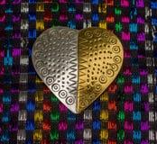 Χρυσή και ασημένια καρδιά ενάντια σε μια ζωηρόχρωμη μεταλλική ύφανση Στοκ Εικόνα