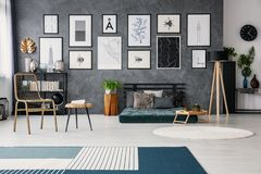 Χρυσή καρέκλα δίπλα στον πίνακα και λαμπτήρας δίπλα στο πράσινο futon στο γκρίζο εσωτερικό διαμερισμάτων με την κουβέρτα Πραγματι στοκ εικόνες