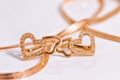 Χρυσή καρδιά σκουλαρικιών που διαμορφώνεται Στοκ Εικόνες