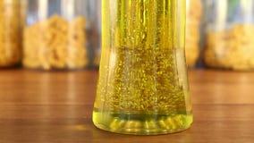 Χρυσή κατεύθυνση αλλαγής φυσαλίδων στο βάζο ελαιολάδου απόθεμα βίντεο