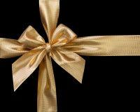 Χρυσή κορδέλλα με το τόξο που απομονώνεται στο μαύρο υπόβαθρο στοκ φωτογραφίες
