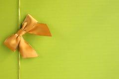 Χρυσή κορδέλλα στην πράσινη ανασκόπηση Στοκ εικόνες με δικαίωμα ελεύθερης χρήσης