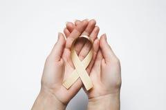 Χρυσή κορδέλλα στα χέρια, καρκίνος παιδικής ηλικίας συμβόλων, ροδάκινο μητρικό γ Στοκ φωτογραφία με δικαίωμα ελεύθερης χρήσης