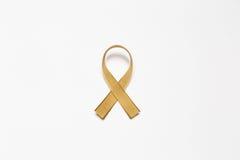 Χρυσή κορδέλλα ως σύμβολο της συνειδητοποίησης καρκίνου παιδικής ηλικίας που απομονώνεται επάνω Στοκ Φωτογραφία