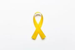 Χρυσή κορδέλλα ως σύμβολο της συνειδητοποίησης καρκίνου παιδικής ηλικίας που απομονώνεται επάνω Στοκ φωτογραφίες με δικαίωμα ελεύθερης χρήσης