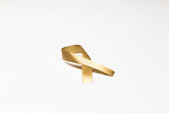 Χρυσή κορδέλλα ως σύμβολο της συνειδητοποίησης καρκίνου παιδικής ηλικίας επάνω Στοκ φωτογραφία με δικαίωμα ελεύθερης χρήσης