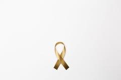Χρυσή κορδέλλα ως σύμβολο της συνειδητοποίησης καρκίνου παιδικής ηλικίας επάνω Στοκ φωτογραφίες με δικαίωμα ελεύθερης χρήσης