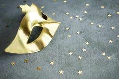 Χρυσή μάσκα με τα αστέρια στο συγκεκριμένο υπόβαθρο Στοκ Φωτογραφία