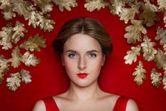 Χρυσή ομορφιά νεολαίας σε ένα κόκκινο υπόβαθρο με τη χρυσή πολυτέλεια Στοκ φωτογραφία με δικαίωμα ελεύθερης χρήσης
