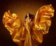 Χρυσή πρότυπη γυναίκα μόδας, πετώντας φτερά υφάσματος μεταξιού στον αέρα στοκ φωτογραφία