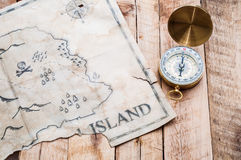 Χρυσή πυξίδα με τον αναδρομικό και εκλεκτής ποιότητας χάρτη του πλαστού νησιού με το στήθος θησαυρών πειρατών Στοκ φωτογραφία με δικαίωμα ελεύθερης χρήσης