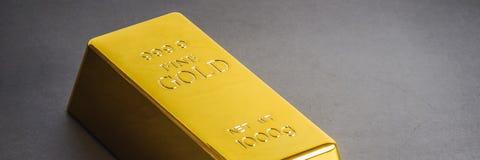 Χρυσή ράβδος πλινθωμάτων φραγμών σε ένα γκρίζο υπόβαθρο Τοποθετημένος διαγώνια στοκ φωτογραφίες