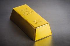 Χρυσή ράβδος πλινθωμάτων φραγμών σε ένα γκρίζο υπόβαθρο Τοποθετημένος διαγώνια στοκ φωτογραφία
