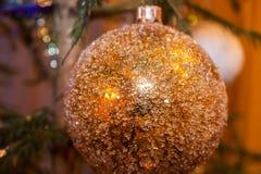 Χρυσή σφαίρα παιχνιδιών Χριστουγέννων κινηματογραφήσεων σε πρώτο πλάνο στοκ φωτογραφία με δικαίωμα ελεύθερης χρήσης