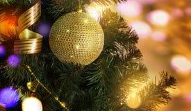 Χρυσή σφαίρα στον κλάδο χριστουγεννιάτικων δέντρων στοκ εικόνες