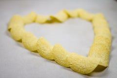 Χρυσή σύνθεση σχηματισμού καρδιών τσιπ πατατών που απομονώνεται πέρα από το ανοικτό γκρι γκρίζο άσπρο υπόβαθρο στοκ φωτογραφίες με δικαίωμα ελεύθερης χρήσης