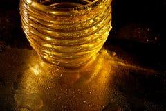 Χρυσή σύσταση με τις πτώσεις νερού Δίψα και η απόσβεσή του Πτώσεις του μελιού στο γυαλί στοκ φωτογραφίες με δικαίωμα ελεύθερης χρήσης