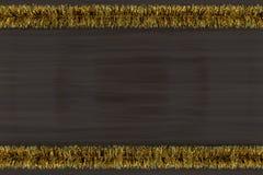 Χρυσή tinsel διακόσμηση στο σκοτεινό ξύλο Στοκ εικόνα με δικαίωμα ελεύθερης χρήσης