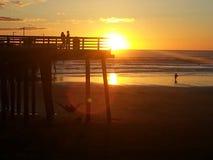 Χρυσοί άνθρωποι ηλιοβασιλέματος στη σκιαγραφία στο Pismo Beach στοκ εικόνες