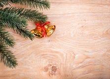 Χρυσοί κουδούνια Χριστουγέννων και κλάδος δέντρων έλατου σε ένα αγροτικό ξύλινο υπόβαθρο Στοκ Φωτογραφίες