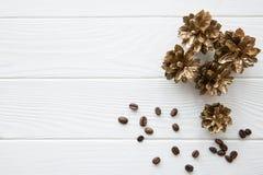 Χρυσοί κώνοι πεύκων με τα φασόλια καφέ στον άσπρο ξύλινο πίνακα backgr στοκ εικόνες