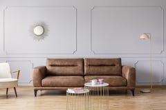 Χρυσοί πίνακες μπροστά από τον καναπέ δέρματος στο γκρίζο κομψό εσωτερικό καθιστικών με τον καθρέφτη και το λαμπτήρα στοκ εικόνες
