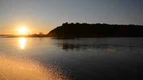 Χρυσοί παφλασμοί του νερού με motorboat που επιπλέει στο ηλιοβασίλεμα απόθεμα βίντεο