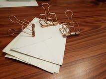 Χρυσοί συνδετήρες εγγράφου μετάλλων για την οργάνωση εγγράφου στο γραφείο Στοκ Εικόνες