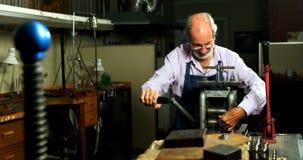 Χρυσοχόος που εργάζεται στη μηχανή στο εργαστήριο 4k φιλμ μικρού μήκους