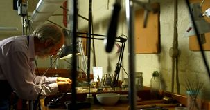 Χρυσοχόος που εργάζεται στο γραφείο στο εργαστήριο 4k απόθεμα βίντεο