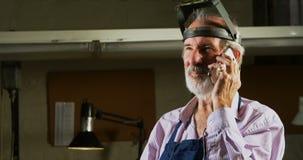 Χρυσοχόος που μιλά στο κινητό τηλέφωνο στο εργαστήριο 4k απόθεμα βίντεο