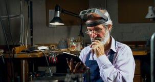 Χρυσοχόος που χρησιμοποιεί την ψηφιακή ταμπλέτα στο εργαστήριο 4k απόθεμα βίντεο
