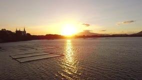 Χρυσός ήλιος που θέτει πέρα από τις δομές μπαμπού καλλιέργειας ψαριών aqua στη λίμνη βουνών φιλμ μικρού μήκους