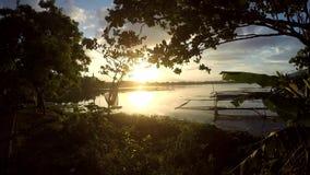 Χρυσός ήλιος που θέτει πέρα από τις δομές μπαμπού καλλιέργειας ψαριών aqua στη λίμνη βουνών απόθεμα βίντεο