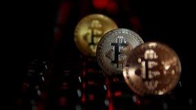 Χρυσός, ασήμι, χαλκός, bitcoin νομίσματα στο υπόβαθρο ενός λάμποντας πληκτρολογίου απόθεμα βίντεο