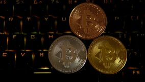 Χρυσός, ασήμι, χαλκός, bitcoin νομίσματα στο υπόβαθρο ενός λάμποντας πληκτρολογίου φιλμ μικρού μήκους