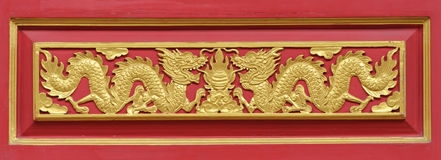 Χρυσός δράκος που διακοσμείται στον κόκκινο τοίχο Στοκ Εικόνες