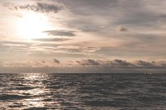 Χρυσός δραματικός ωκεάνιος ουρανός με τον ήλιο που απεικονίζεται Στοκ Φωτογραφίες