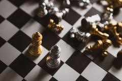 Χρυσός και ασημένιος βασιλιάς παιχνιδιών σκακιού που μένει στη σκακιέρα στοκ φωτογραφία με δικαίωμα ελεύθερης χρήσης