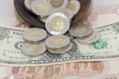 Χρυσός και ασημώστε νομίσματα 1 τα αιγυπτιακά μετάλλου λιβρών σε ένα χαρτί τραπεζογραμματίων ΑΜΕΡΙΚΑΝΙΚΩΝ δολαρίων Στοκ Εικόνες