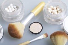 Χρυσός και μαργαριτάρι highlighter υπό μορφή σφαιρών σε ένα ανοικτό βάζο Κοντά στη βούρτσα για την εφαρμογή των καλλυντικών Σε μι Στοκ Φωτογραφίες