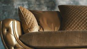 Χρυσός καναπές πολυτέλειας σε ένα υπόβαθρο σοφιτών φιλμ μικρού μήκους