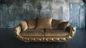 Χρυσός καναπές πολυτέλειας σε ένα υπόβαθρο σοφιτών απόθεμα βίντεο