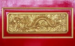 Χρυσός κινεζικός δράκος στο κόκκινο ξύλο Στοκ Εικόνα