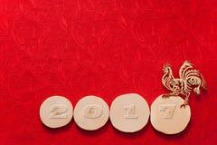Χρυσός κόκκορας και ημερομηνία του 2017 στο πριόνι τεσσάρων κληθρών που κόβεται στο κόκκινο στοκ εικόνες