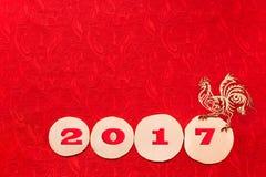 Χρυσός κόκκορας και κόκκινη ημερομηνία 2017 στο πριόνι κληθρών που κόβεται στο κόκκινο υπόβαθρο στοκ φωτογραφία